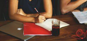 Afbeelding van schrijvende dame met laptop en notitieblok